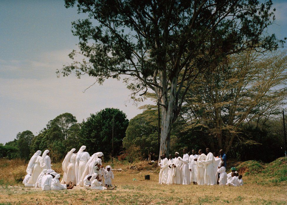 Group of people dressed in white next to a tree