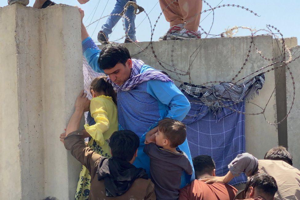 Οι άνθρωποι αγωνίζονται να διασχίσουν το τείχος του διεθνούς αεροδρομίου Hamid Karzai για να φύγουν από το Αφγανιστάν στις 16 Αυγούστου 2021