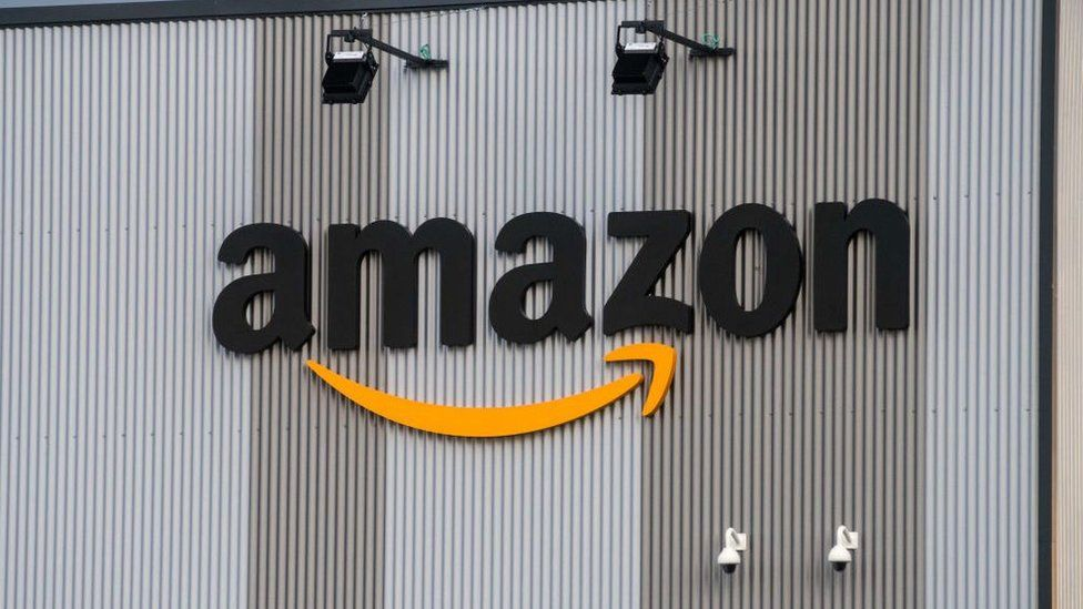 The Amazon logo is seen on the exterior steel cladding of an industrial building in this close-up shot
