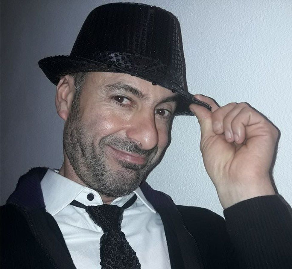 A picture of Andrea Cerulli smiling in a black sequinned trilby hat