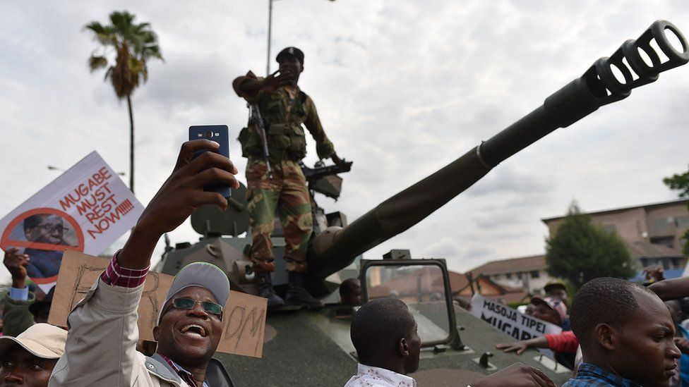 A man takes a selfie-picture of a Zimbabwean Defence Force soldier standing on a tank during a march in the streets of Harare, on November 18, 2017 to demand to the 93 year-old Zimbabwe's president to step down