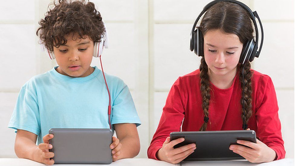 A boy and girl using tablets