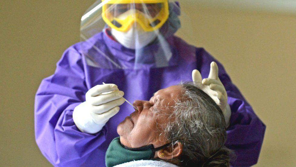 Медицинский работник в средствах индивидуальной защиты (СИЗ) собирает образец мазка.