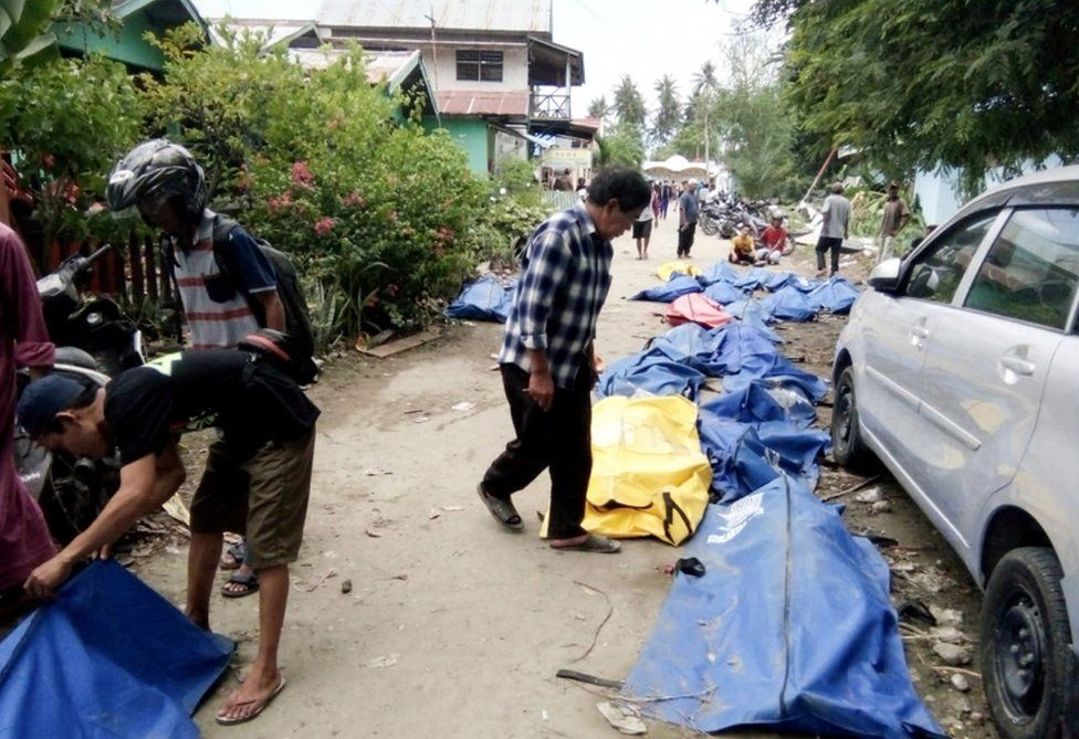 Locals check bodybags as they search for their families in a Palu street