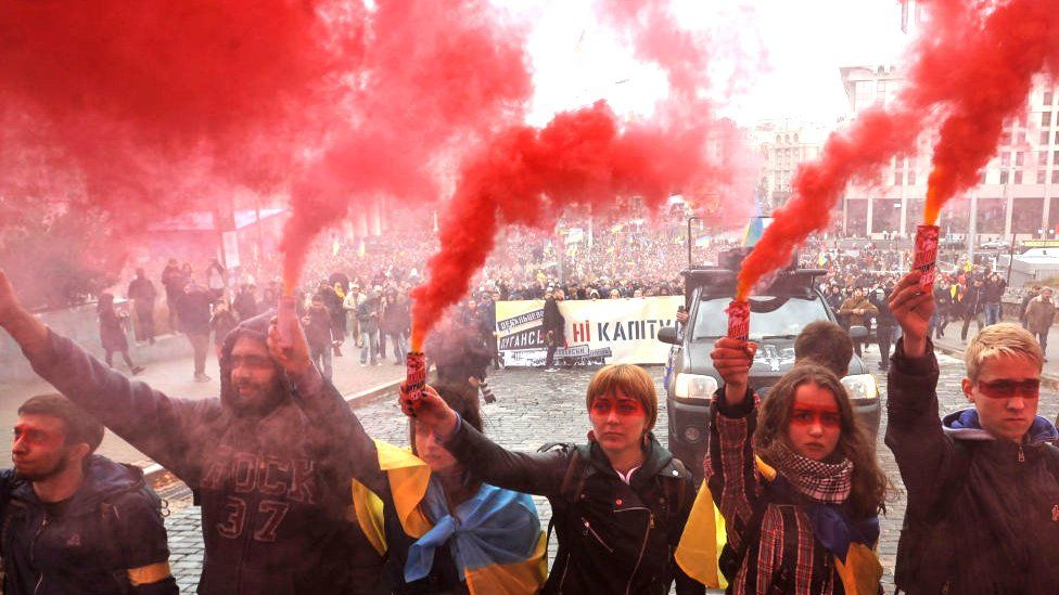 Protesters holding smoke grenades in Kyiv