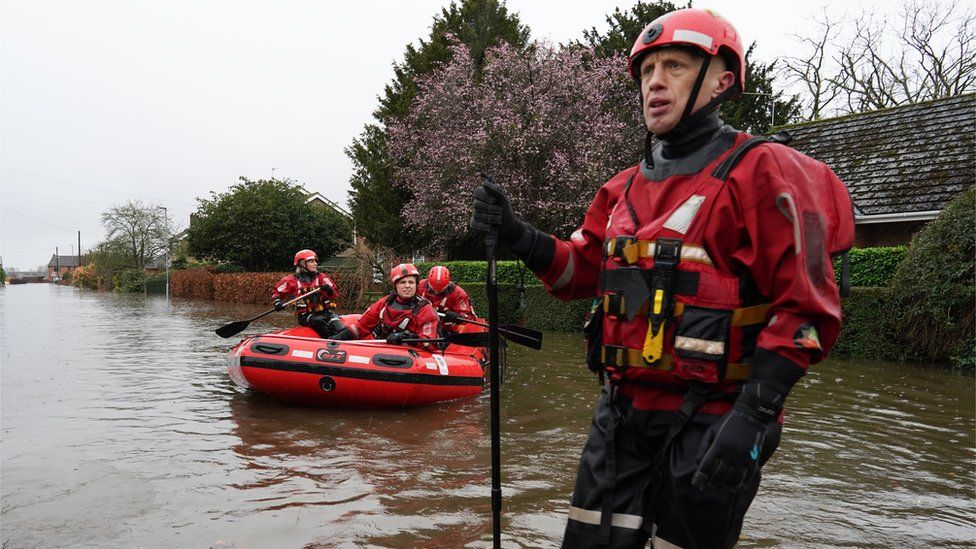 Humberside Fire and Rescue service search along a flooded street for residents after the River Aire bursts its banks
