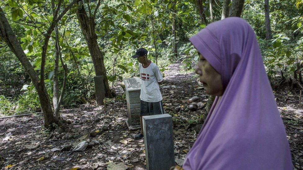 Relatives visit the site that is believed to be the burial ground for victims of a 1965 massacre