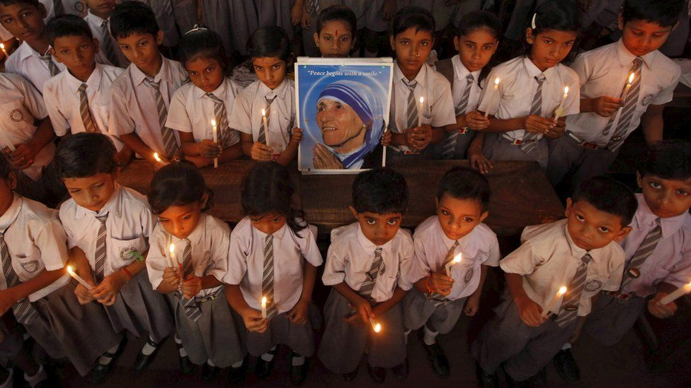 School children take part in a candlelight prayer ceremony as they hold a portrait of Mother Teresa on the occasion of her 101st birth anniversary celebrations in Kolkata, India