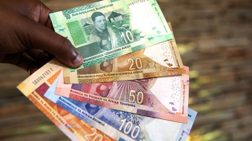 A man holding South African rand notes