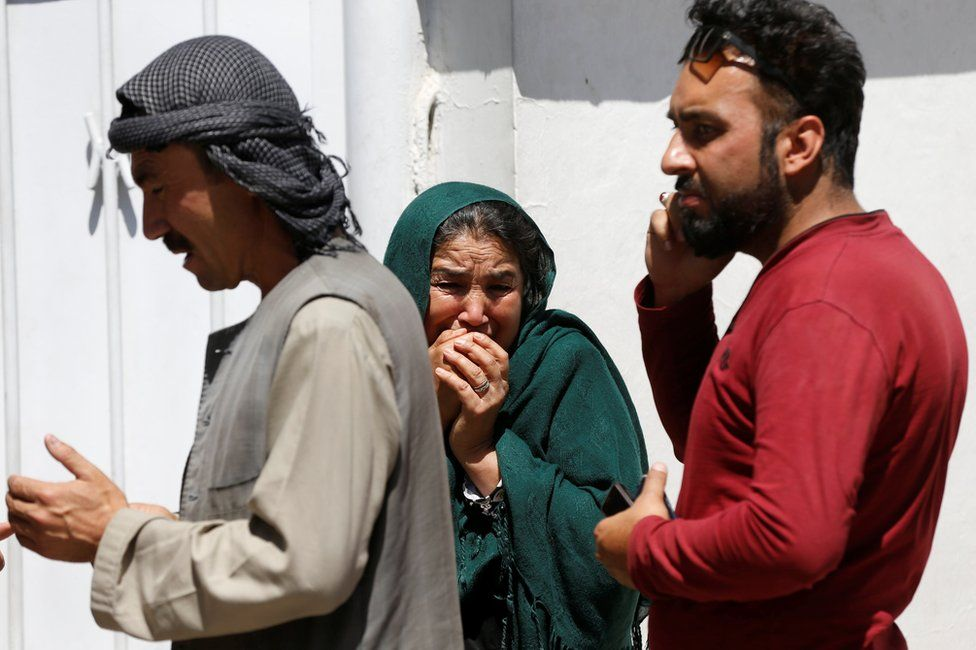 Relatives of Afghan victims mourn outside a hospital after the blast in Kabul, 31 May