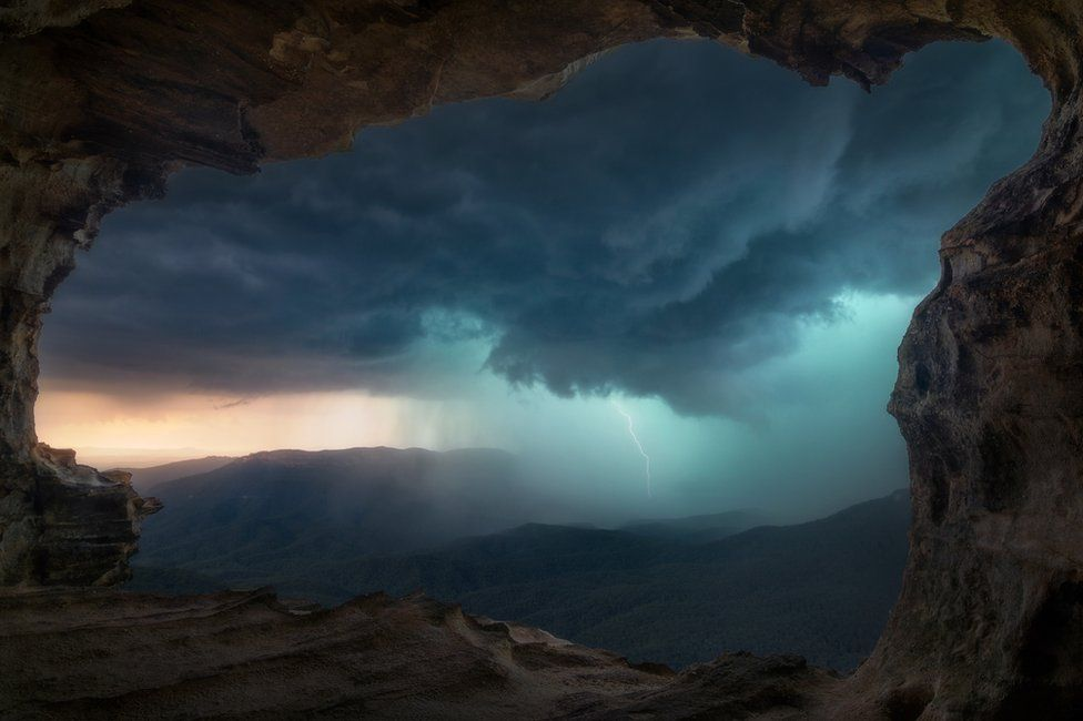 A mountainous landscape with lightning in the background