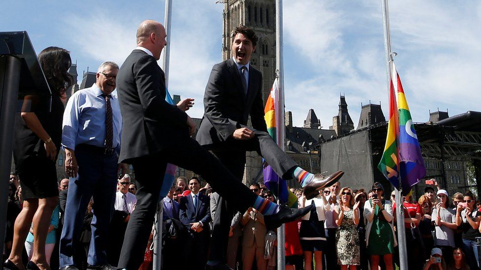 Canada's Prime Minister Justin Trudeau compares socks with Liberal MP Randy Boissonnault during a pride flag raising ceremony on Parliament Hill in Ottawa, Ontario, 25 June 2017