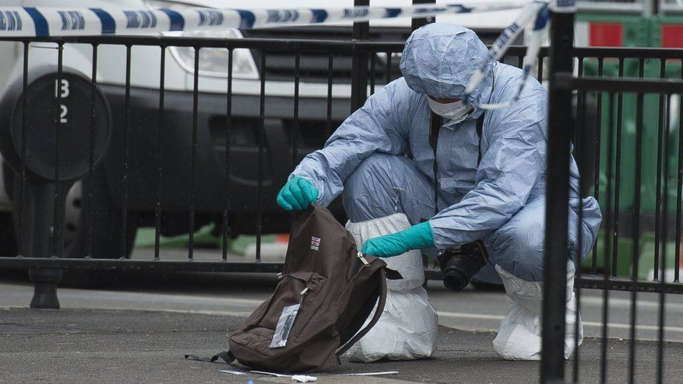 A forensics officer examining a rucksack