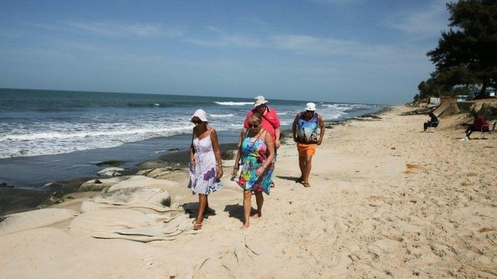 British tourists walking on Gambian beach