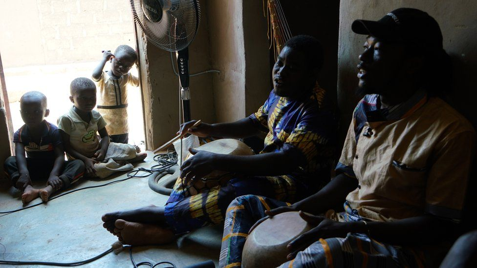 (Right to left) Maboudou Sanou and Ibrahim Dembélé sing during a rehearsal in the home Sanou shares with composer Keiko Fujiie, a week before the premiere of the opera Là-bas ou Ici (Here or There) in Ouagadougou. Sanou's son and children from the neighbourhood listen.