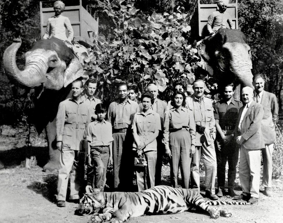 A black and white picture from 1961 shows the Queen, Prince Philip, the Maharaja and Maharani of Jaipur, India, and several others, standing in front of a tiger he had killed