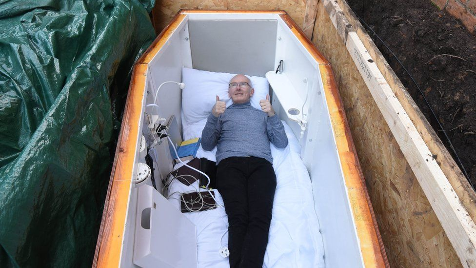 The coffin has been specially adapted so he can broadcast live on social media from underground.