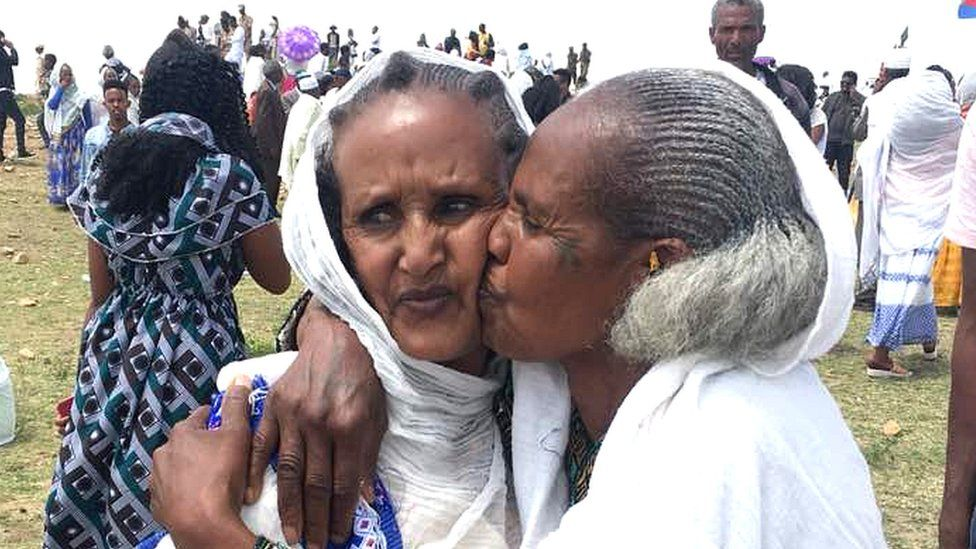 One woman kissing another on the cheek