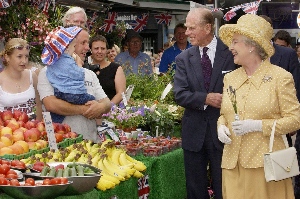 Queen Elizabeth II (right) and the Duke of Edinburgh (centre right) visit market stalls in Kingston town centre, during the Queen's Golden Jubilee visit to West London