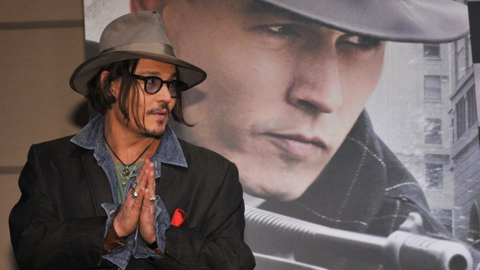 US actor Jonny Depp stands in front of a Public Enemies film poster in Tokyo, Japan. Photo: 9 December 2009