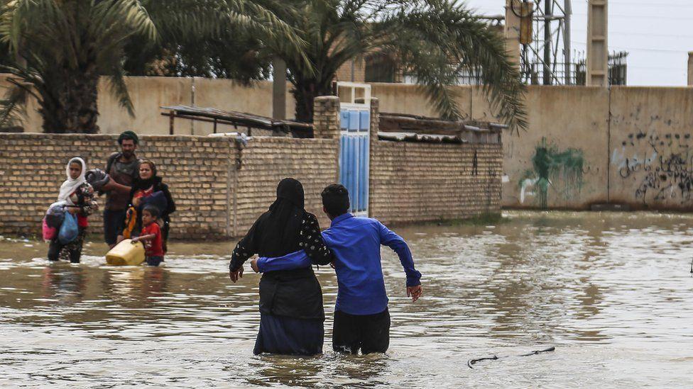 Iranians walk through floodwaters after unprecedented rains, March 2019