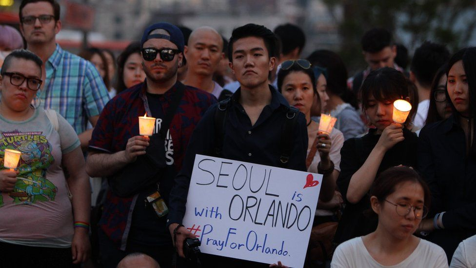 People gather during a vigil in downtown Seoul to remember victims of the shooting at an Orlando nightclub on June 13, 2016 in Seoul, South Korea