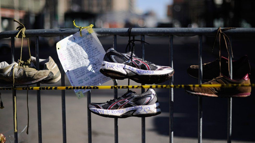 Running shoes are placed at a makeshift memorial for victims near the finish line of the Boston Marathon bombings at the intersection of Newbury Street and Darthmouth Street two days after the second suspect was captured on April 21, 2013 in Boston, Massachusetts.