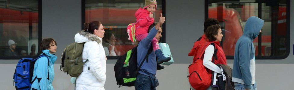 Migrants walk on a platform after their arrival at the main railway station in Munich, southern Germany, on 6 September 2015
