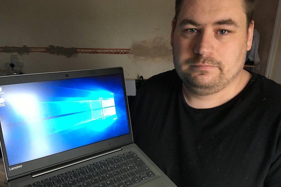 Shaun Coffell holding the laptop
