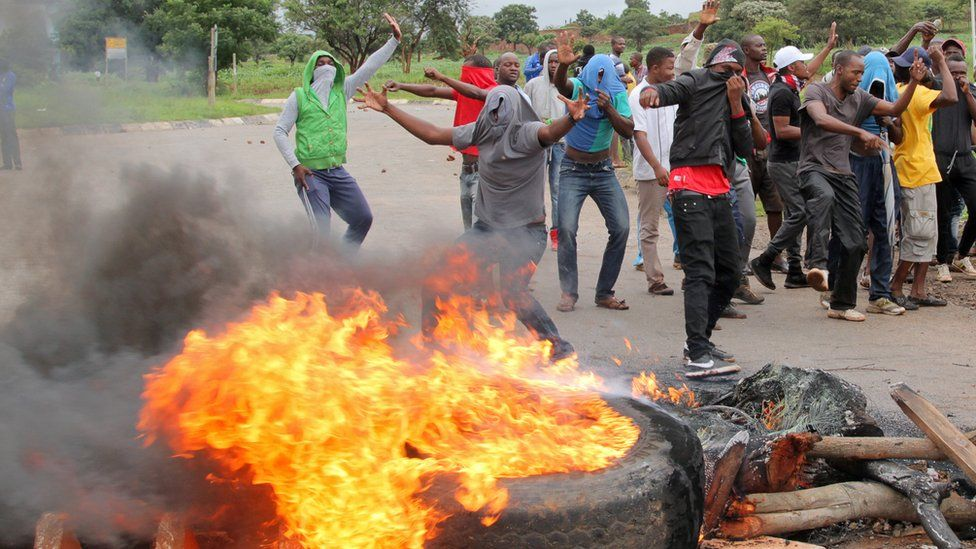 Protesters stand behind a burning barricade during protests on a road leading to Harare, Zimbabwe, January 15, 2019.