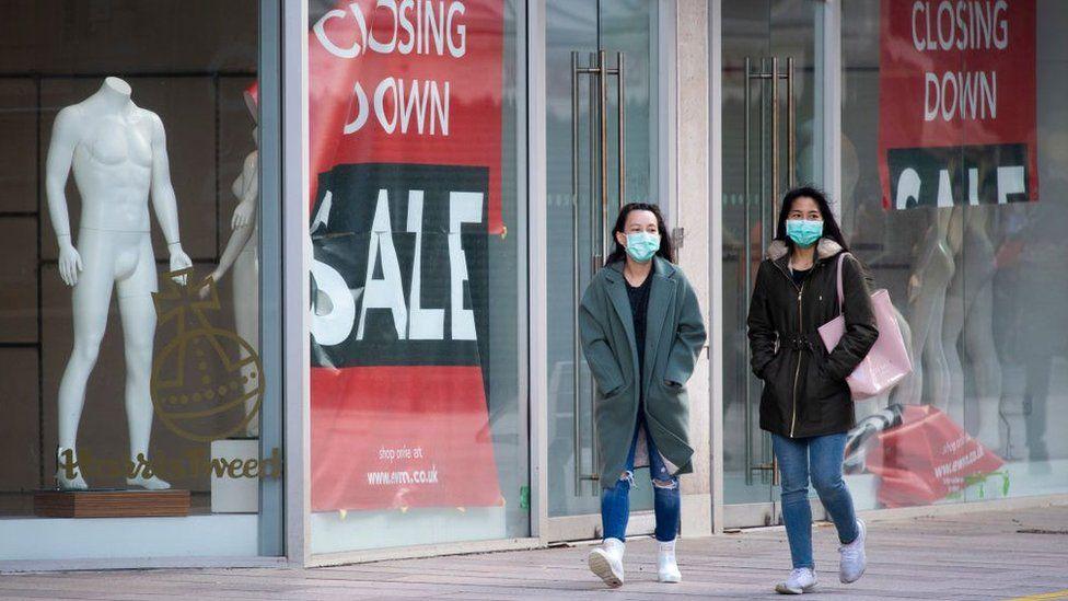 two women walking past closed shop