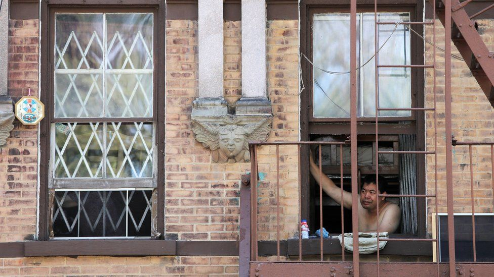 A man looks outside his window in New York