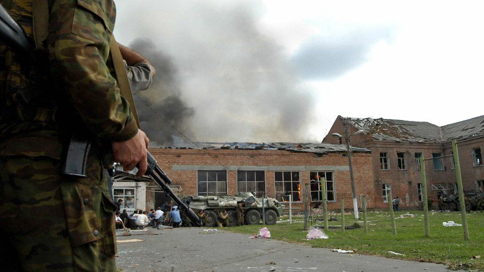 Soldiers and security forces are seen in front of the burning school during the rescue operation in Beslan, northern Ossetia