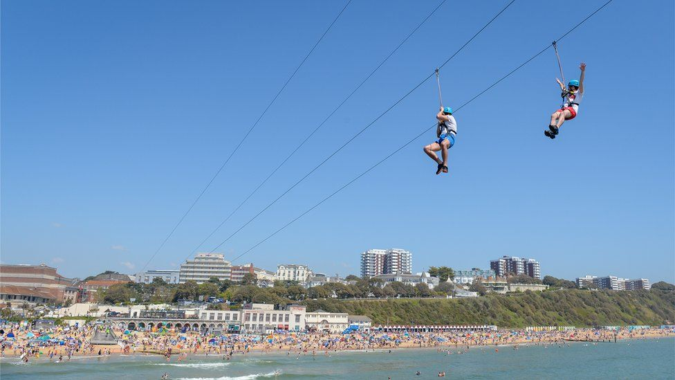 People enjoy the zip line ride on the beach at Bournemouth beach on Bank Holiday Monday