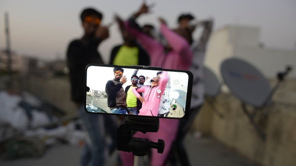 Youths act in front of a mobile phone camera while making a TikTok video on the terrace of their residence in Hyderabad, February 2020