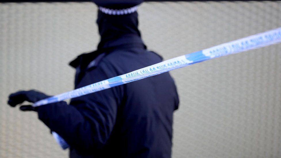 A police officer marks a cordon after a fatal stabbing in Hackney on 5 April 5 2018 in London