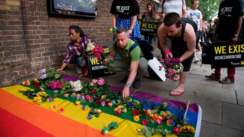 People leave flowers at demonstration at Russian embassy in London