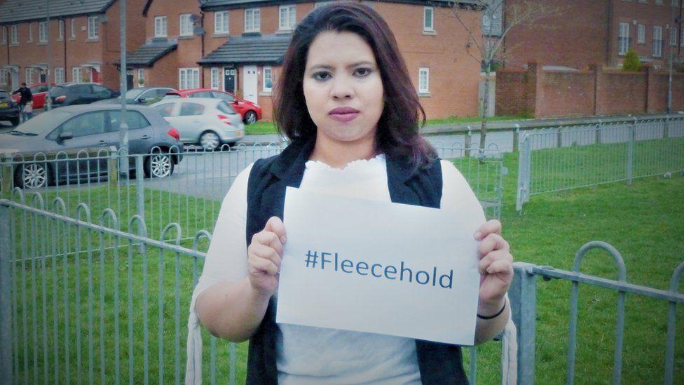 Halima Ali holding a sign saying #Fleecehold