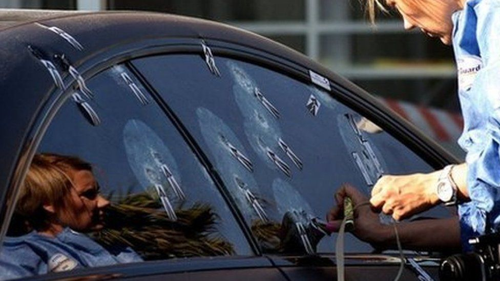 Unidentified ballistics investigator comb the scene of Radovan Krejcir's bullet-proof car after he escaped an attempt to kill him in Johannesburg, South Africa, Wednesday July 24, 2013.