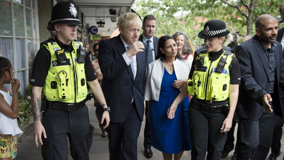 Prime Minister Boris Johnson and Home Secretary Priti Patel on a walkabout with local police during a visit to North Road, Harbourne, Birmingham