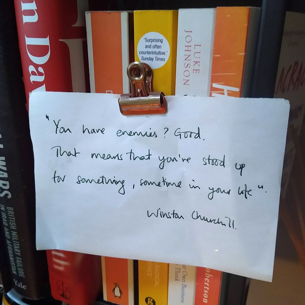 A note stuck to the book case