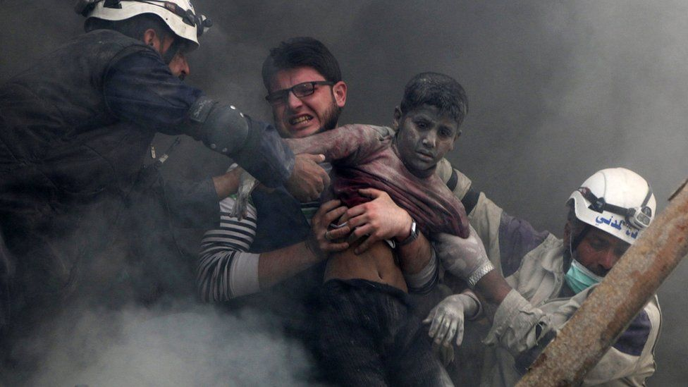 Men rescue a boy from under the rubble of a destroyed building after a reported government air strike in the rebel-held Shaar district of Aleppo, Syria (6 April 2014)