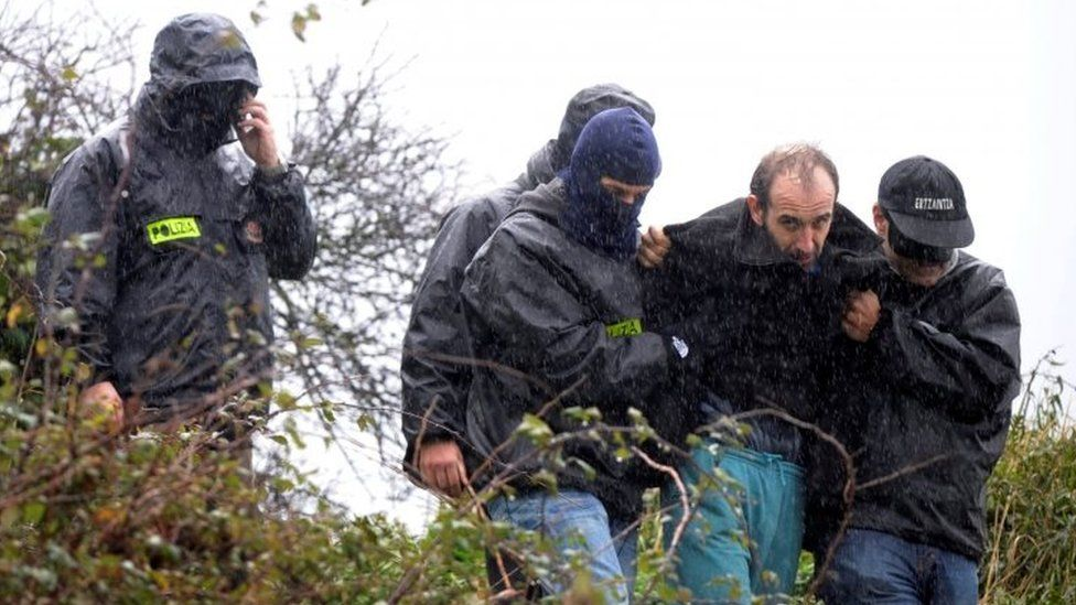 Basque police lead suspected leader of an ETA cell away from an arms and explosives hide ollowing a search in woods near the fishing town of Ondarroa, Spain (29 January 2010)