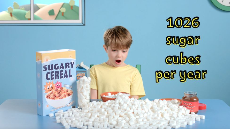 A boy surrounded by sugar cubes at breakfast and a packet of sugary breakfast cereal