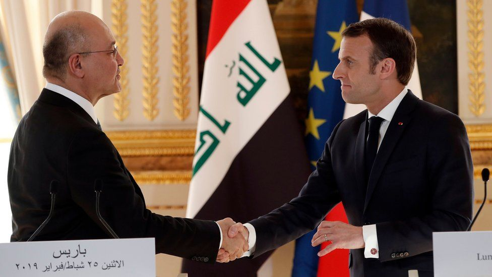 French President Emmanuel Macron (R) shakes hands with Iraqi President Barham Saleh as they attend a press conference at The Elysee Palace in Paris on February 25, 2019.