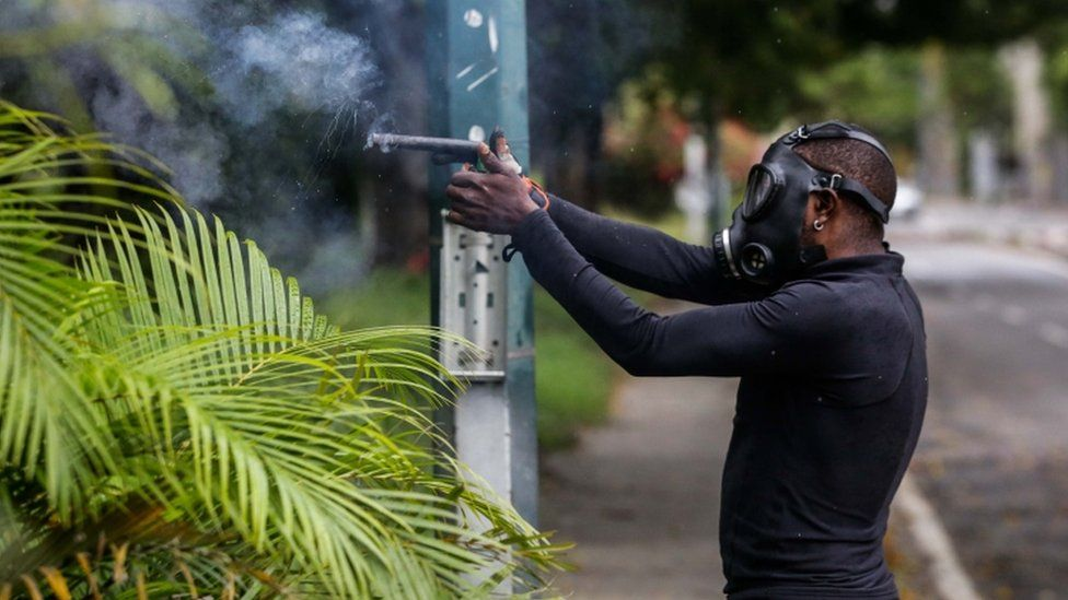 A protestor confronts members of the National Bolivarian Guard during a demonstration against the vote for a Constituent Assembly in Caracas, Venezuela, 30 July 2017