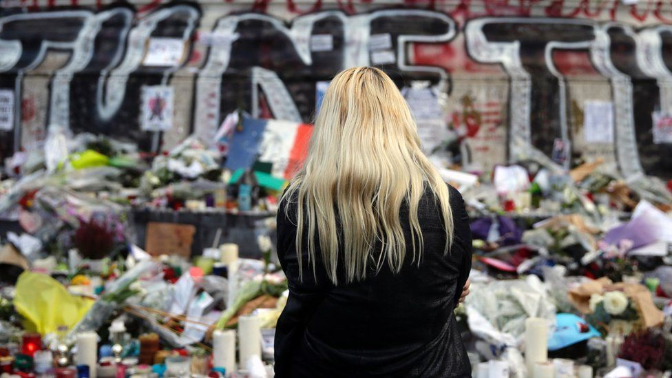 A woman stands in front of a makeshift memorial