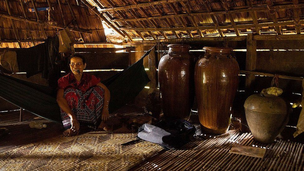 A woman from the Bunong indigenous group sits beside jars of rice wine in her home on August 8, 2014 in Mondulkiri, Cambodia