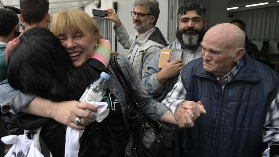 Carlos Gareis (right), a former Ford worker and a political prisoner, holds the hand of his daughter Estela (centre) after the court's verdict in Buenos Aires, Argentina. Photo: 11 December 2018