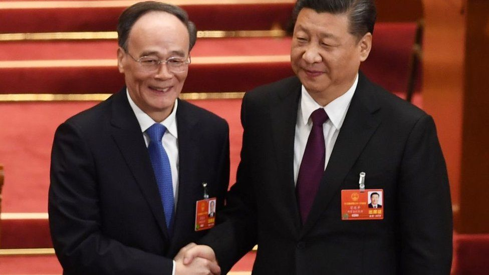Wang Qishan, left, shakes hands with President Xi Jinping after becoming his deputy
